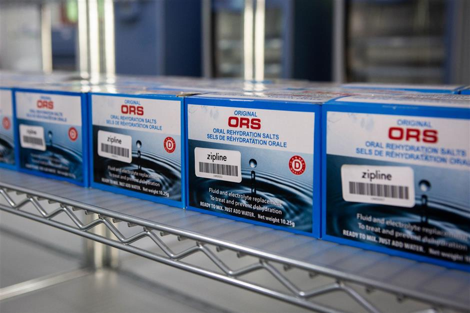 Packages of oral rehydration salts (ORS) are seen on a shelf during preparations for a delivery at the drone delivery service base run by operator Zipline in Omenako, 70 kilometres (40 miles) north of Accra on April 23, 2019. - Ghana launched a fleet of drones on April 24, 2019 to carry medical supplies to remote areas, with Ghana's President declaring it would become the 'world's largest drone delivery service.' The craft are part of an ambitious plan to leapfrog problems of medical access in a country with poor roads. The drones have been flying test runs with blood and vaccines, but the project was officially inaugurated Wednesday at the main drone base in Omenako, 70 kilometres (40 miles) north of Accra. Operator Zipline, a US-based company, said the three other sites should be up and running by the end of 2019. The drones are planned to ferry 150 different medicines, blood, and vaccines to more than 2,000 clinics serving over 12 million people -- roughly 40 percent of the population. (Photo by Ruth McDowall / AFP)