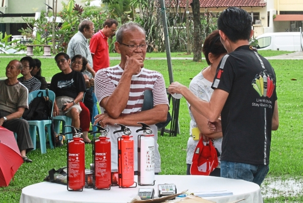 A resident looking at a range of fire extinguishers on display during the workshop.