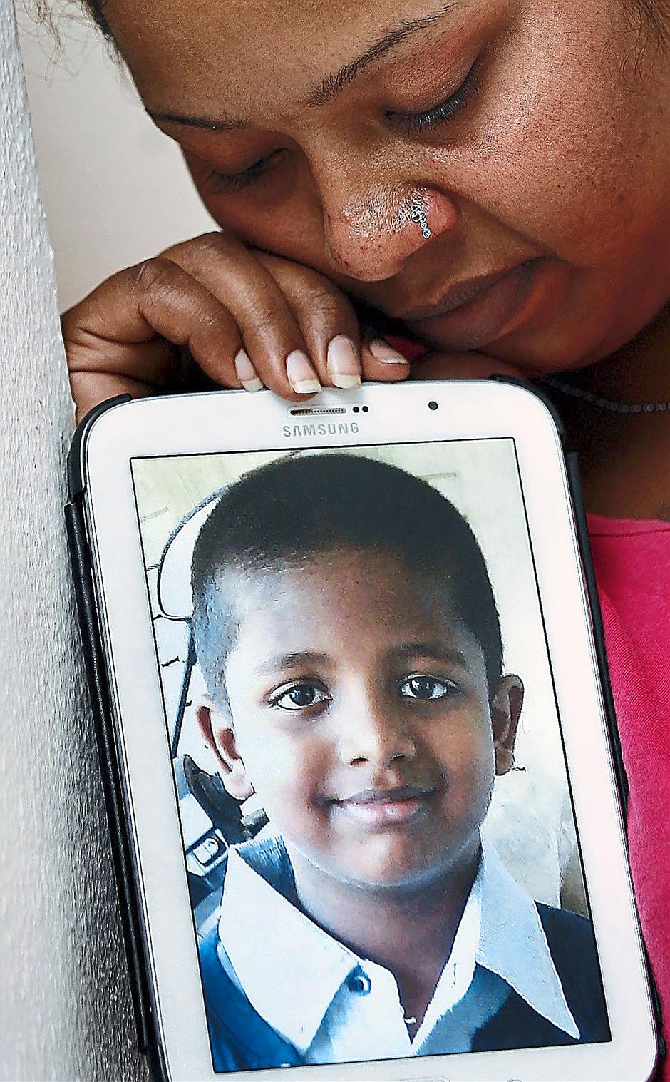 Missing him: S. Deepa with daughter V. Sharmila  and a picture of her six-year-old son V. Mithran aka Nabil Izwan Abdullah. - UU BAN LEONG/The Star