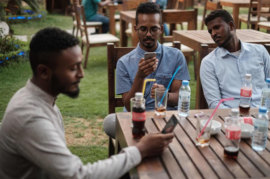 Sudanese Mohamed Omar (L), 25, sits near his friends at a cafe in which an hour of internet costs 50 Sudanese pounds, which is approximately one US dollar, on June 17, 2019 in an upscale Khartoum district. - Internet on mobile phones and fixed land connections has been widely cut across Sudan since the violent dispersal of a protest camp outside army headquarters on June 3 that left dozens dead and hundreds wounded. The ruling military council imposed the blackout to prevent further mobilisation of protesters, according to users. (Photo by Yasuyoshi CHIBA / AFP)