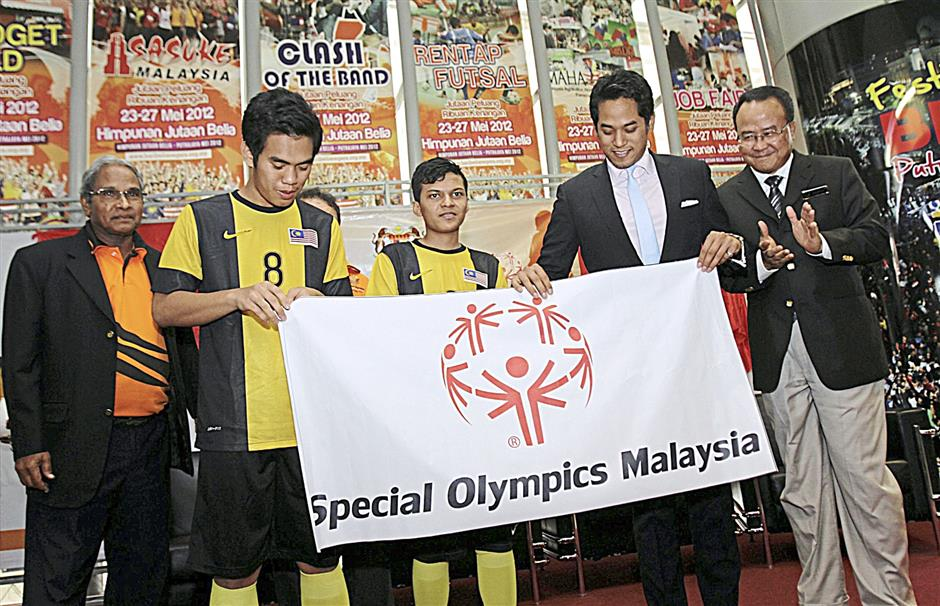 Special Olympics Malaysia vice-president Peter Vellapan (left most), Khairy Jamaluddin (second from right) and National Sports Council director-general Zolkples Embong (right most) with the youths during the soft launch of the Special Olympics Unified Football World Cup 2014 at the Ministry of Youth and Sports in Putrajaya