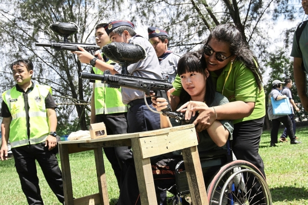 Wheelchair-bound Lim Chun Tian guided by a volunteer while playing paintball.