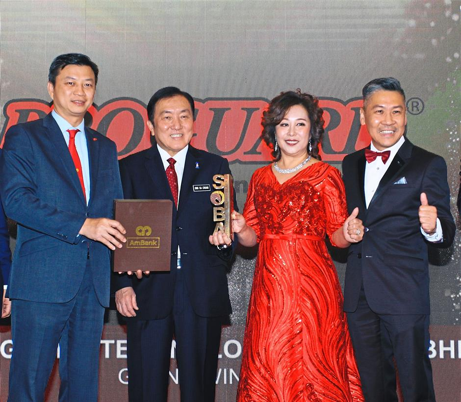 Yap presenting the Platinum award for Malaysian Business of the Year to Datuk Lee Ngai Mun and Datin Cindy Choh of Proguard Technologies (M) Sdn Bhd while International Trade and Industry Minister II, Datuk Seri Ong Ka Chuan looks on.