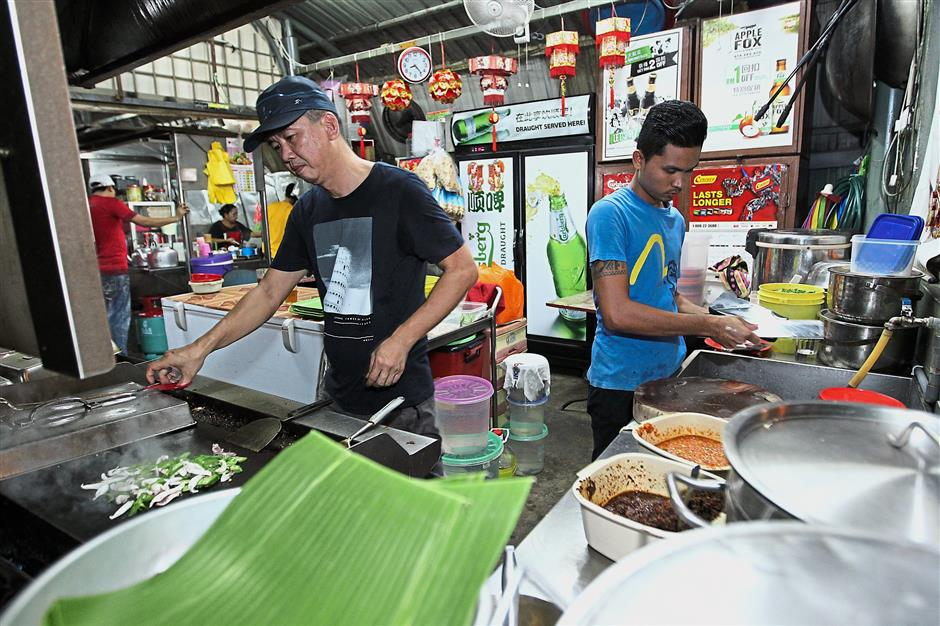 The cook, known as Ah Keong (left) preparing the grilled fish for customers.