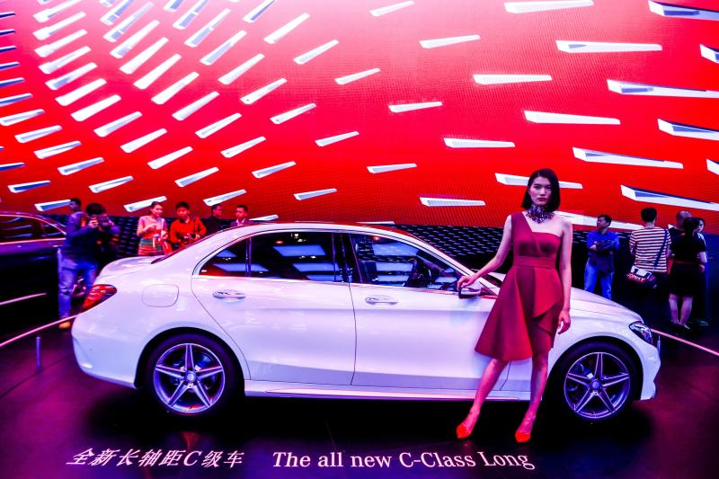 A model stands next to the new Mercedes Benz C-Class Long at the China International Exhibition Center in Beijing in April 2014. For years, Mercedes has lagged behind Audi and BMW in the China market, but now it has decided to make a big push, even if it means transferring technological know-how - EPA Photo.