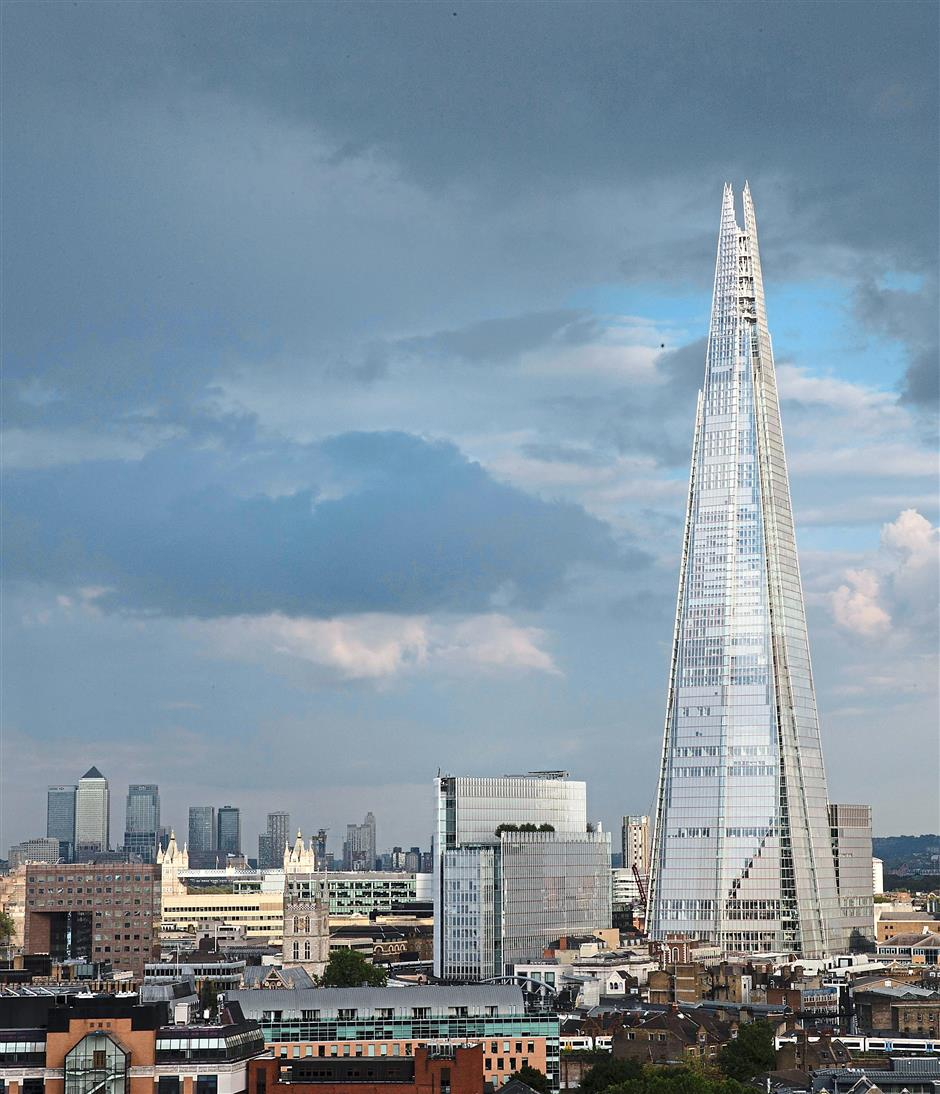 New base: The Shard building is seen in front of dark clouds in central London. Khazanah joins nine other new tenants in The Shard who have signed leasing deals this year, leaving office spaces almost 90 fully occupied. — Reuters