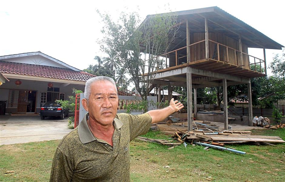Better safe than sorry: Phan Kieng Foo, from Manek Urai Lama, Kelantan, built an elevated wooden shelter next to his house after the floods. He plans to keep his valuables there if floods strike again this year.