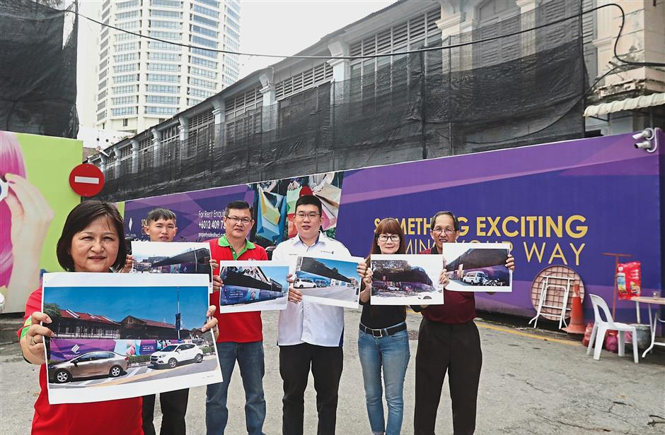 Under wraps: (Above) A purple hoarding covering a row of heritage buildings at the junction of Jalan Gurdwara-Lebuh Noordin. (Right pic, on the left) Ng and her team showing more photos of buildings covered with purple hoardings while standing in front of a sealed up property in Bertam Lane. — ZHAFARAN NASIB/The Star