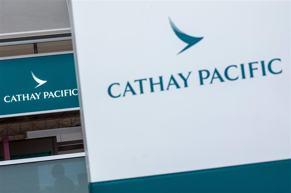 Signage for Cathay Pacific Airways Ltd. stands near the airline\'s check-in counter at Hong Kong International Airport in Hong Kong, China, on Tuesday, March 5, 2019. Cathay is scheduled to release annual earnings on March 13. Photographer: Paul Yeung/Bloomberg