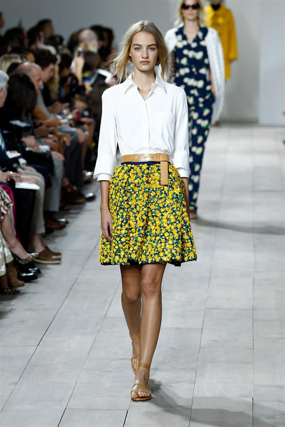 A crisp white shirt tucked into an above the knee 3D floral applique skirt with a light tan leather belt.