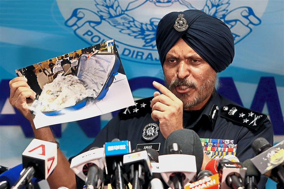 Amar Singh, head of Malaysias Commercial Crime Investigation Department (CCID), displays a photo of items from a raid during a news conference in Kuala Lumpur, Malaysia June 27, 2018. REUTERS/Lai Seng Sin