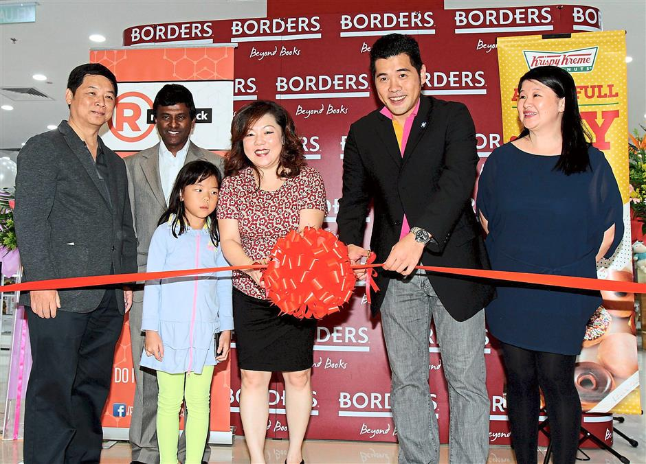 Grand opening: Yau (third from right) and IOI City Mall head of marketing and leasing Chris Chong (second from right) cutting a ribbon to mark the opening of Borders and RadioShack at IOI City Mall. With them are (from left) Tan, Xavier, Yau's daughter Teoh Zhi Lin and Chuah.