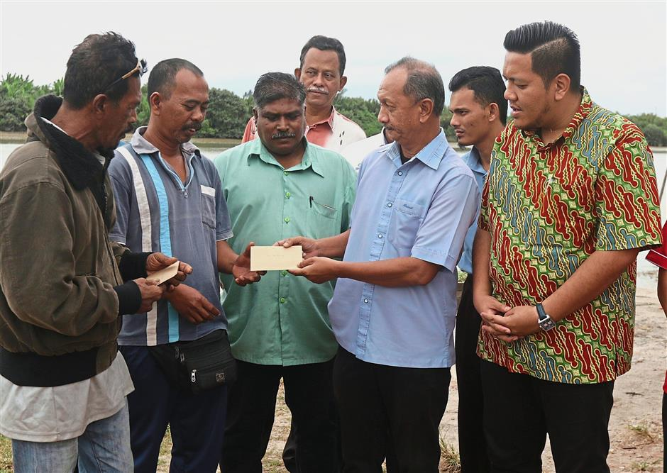 Mahadi (second right) presenting the cash aid to (from left) Ismailand Norazmi. Looking on is Dr Afif (in batik shirt).