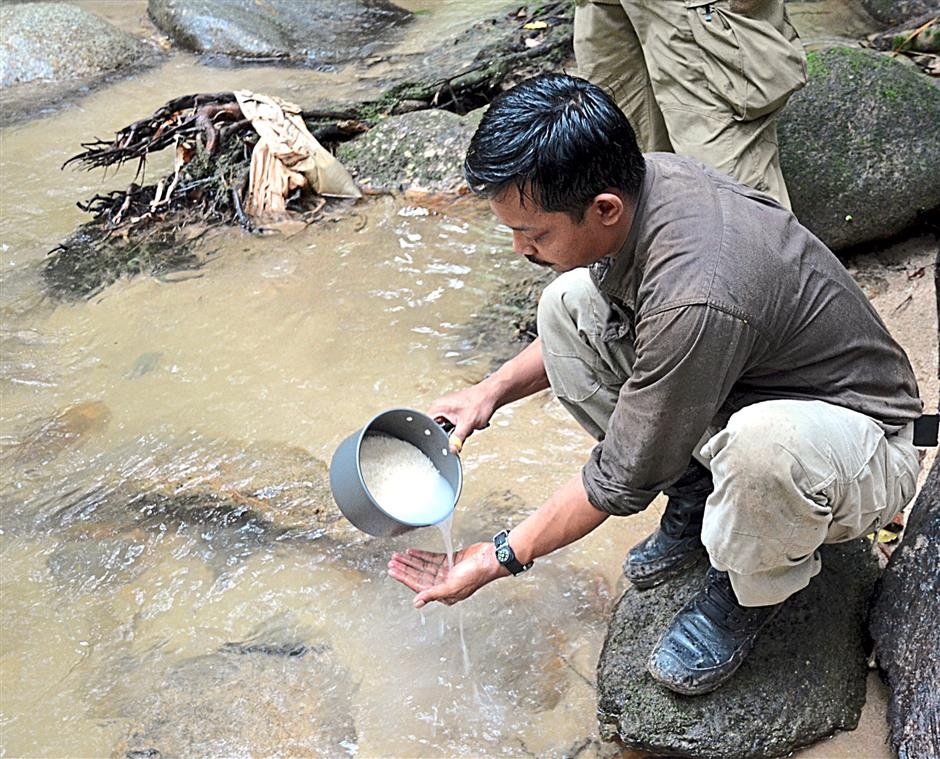 Outdoor instructor Vee demonstrating using running river water to wash rice.