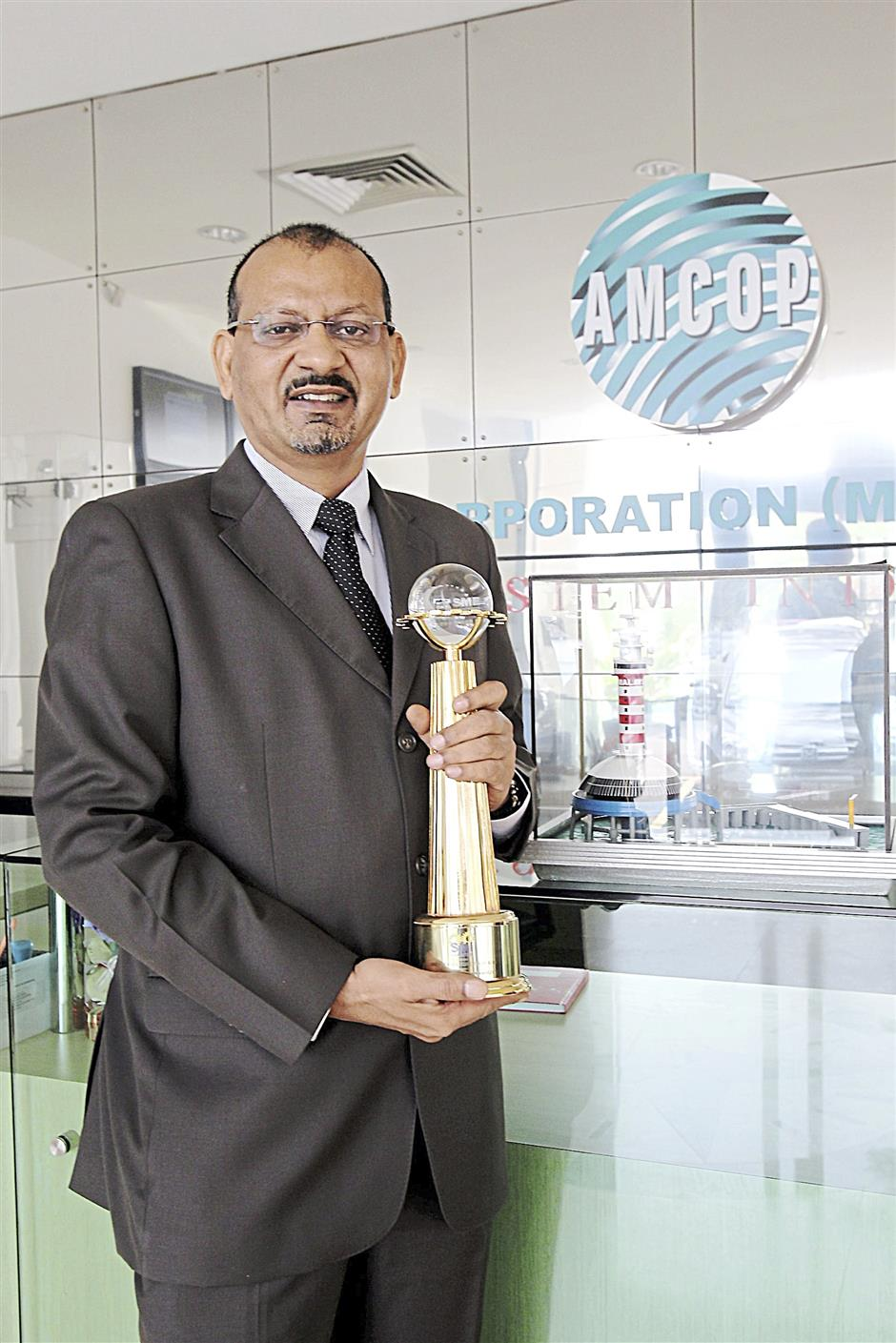 Mustaffa holding the SME Service Excellence Award 2012 received from SMI Association of Malaysia. He is standing beside a model of One Fathom Bank radar system.