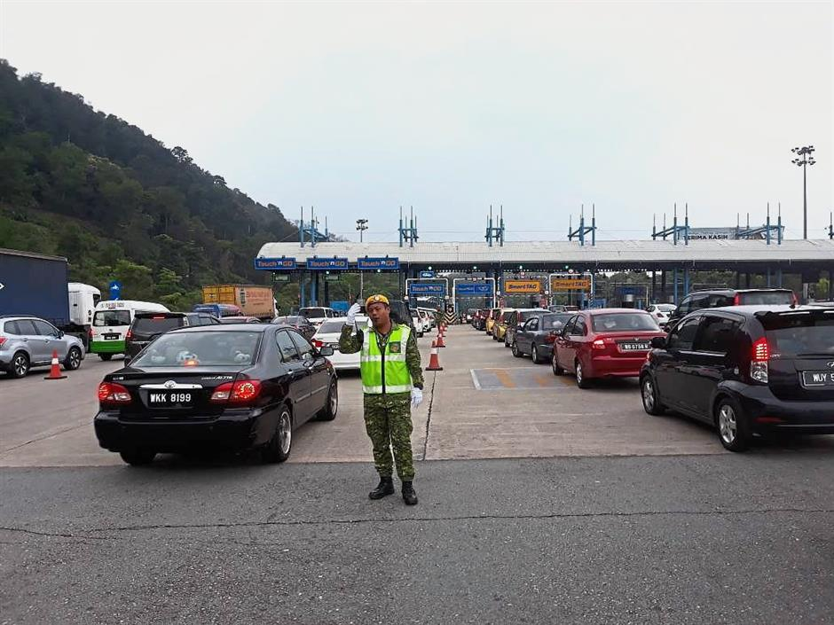 Come rain or shine: A Rela personnel on duty to ensure smooth traffic flow at the Gombak Toll Plaza.
