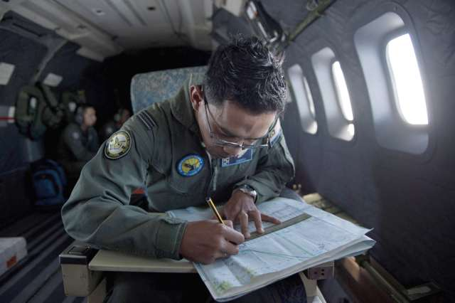 Royal Malaysian Air Force Kapt Azam Fareq Hassan working in a map onboard a CN235 aircraft during the search and rescue operation to fing the missing Malaysia Airlined Flight MH 370 plane over the Straits of Malacca.-AFP