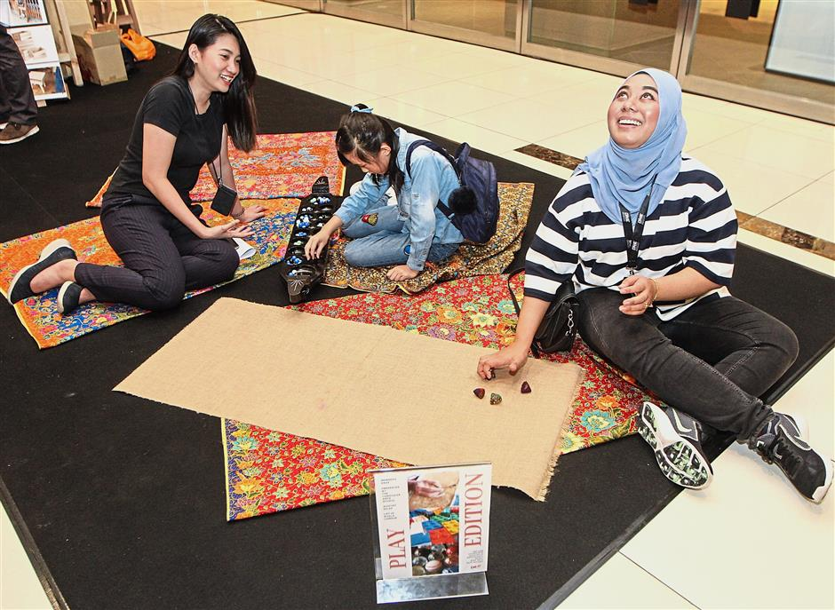 Visitors can play traditional games such as congkak (left) and batu seremban (right) at the mall this month.