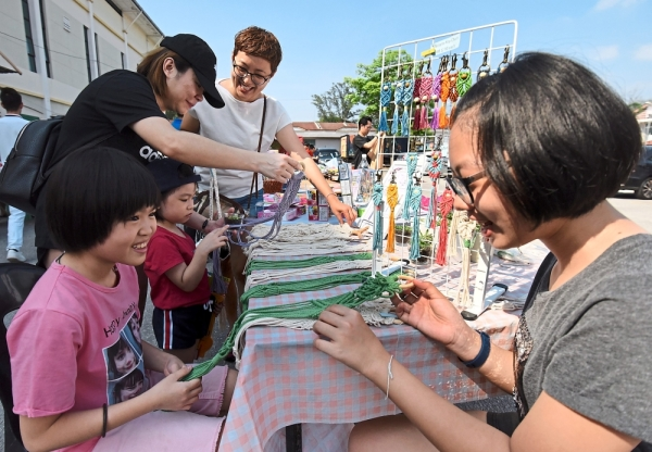 Felicia Yew, 12, (from right) helping her mother Sammi Ooi, 38, at their 'Macrame Patch Workshop' boothduring the car boot event.