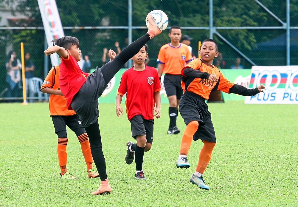 An SDFC player attempts to win the ball in mid air against his opponent from MBJ United.— Photos: FAIHAN GHANI/ The Star