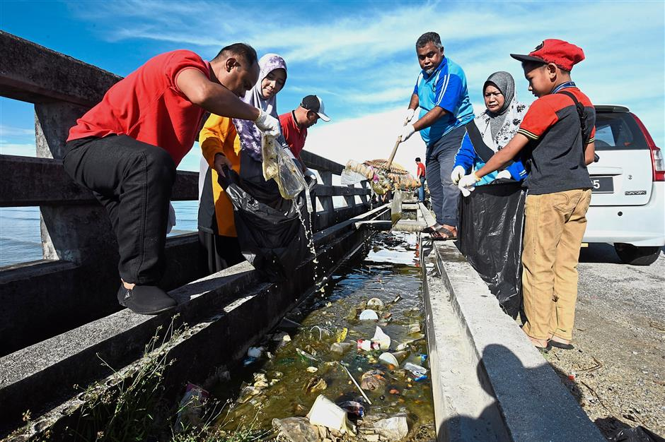 (Above) Mohd Faris made the gotong-royong suggestion on FB which garnered many likes and support. (Left) Participants including families with children helping to remove rubbish clogging the drains along the bridge to Pulau Bunting.(Below) A view of the bridge to Pulau Bunting and picnickers in Pulau Bunting. — Photos: MUSTAFA AHMAD/The Star