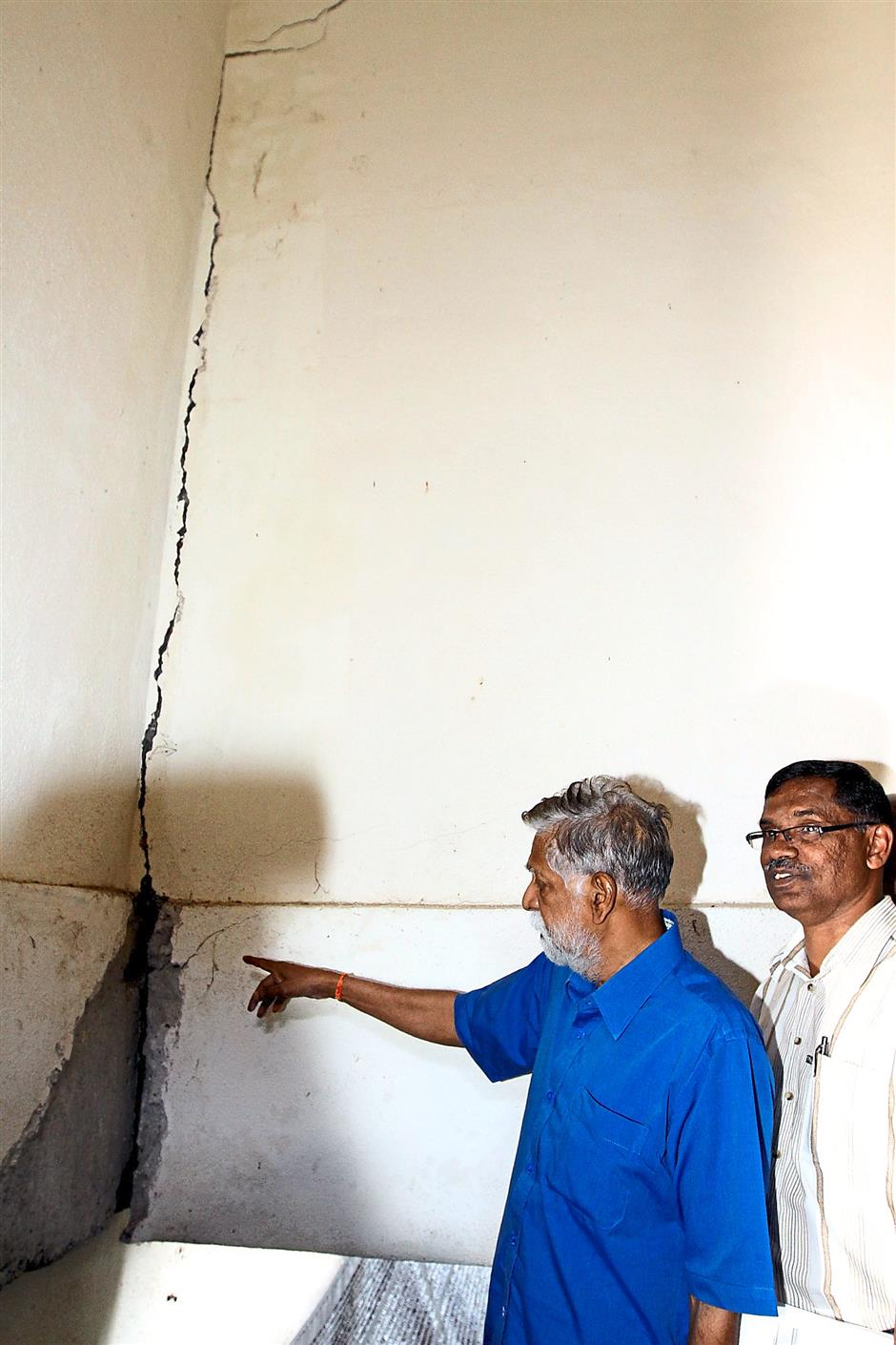 Damaged walls: Palanivel taking a closer look at the deep cracks which have appeared at the living skills block at SMK Ringlet during his visit to the school.