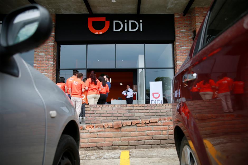 The logo of Chinese ride-hailing firm Didi Chuxing is seen as employees stand outside the new drivers center in Toluca, Mexico, April 23, 2018. REUTERS/Carlos Jasso