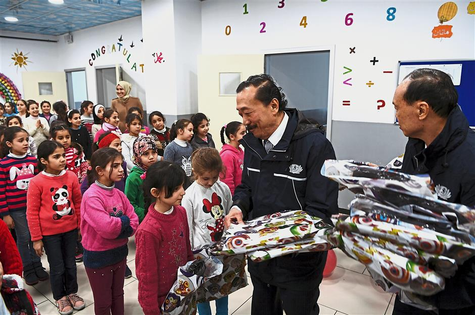 Victims of war: Tan (second from right) and Lim giving out schoolbags to Syrian children at the El Menahil International School in Istanbul. u2014 Bernama