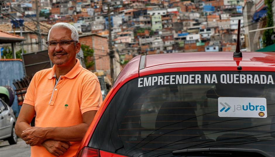 Brazilian Alvimar da Silva, creator of the JaUbra (Uber of slum) private transportation service, poses next to his car in Brasilandia, northern outskirts of Sao Paulo, Brazil, on February 27, 2019. - The JaUbra application was created for a slum where Uber does not cover. (Photo by Miguel SCHINCARIOL / AFP)