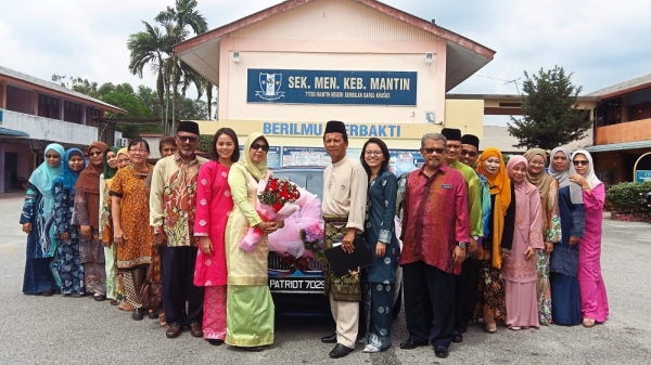 Noru2019aini (in beige) and her husband Ariffin (10th right) pose with several teachers at her retirement ceremony.