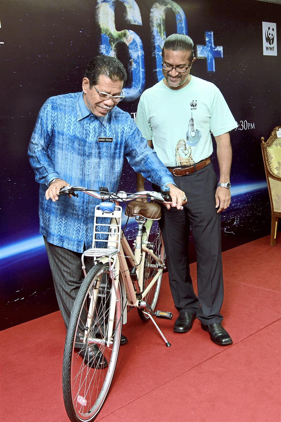 Healthy option: Ahmad Phesal (left) checking out a bicycle after pledging to increase the number of cycling routes. With him is Dionysius.