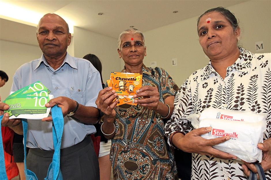 Arumugam with his wife Leevathy, (middle) and daughter Ratha, holding their goodies and T-shirts.