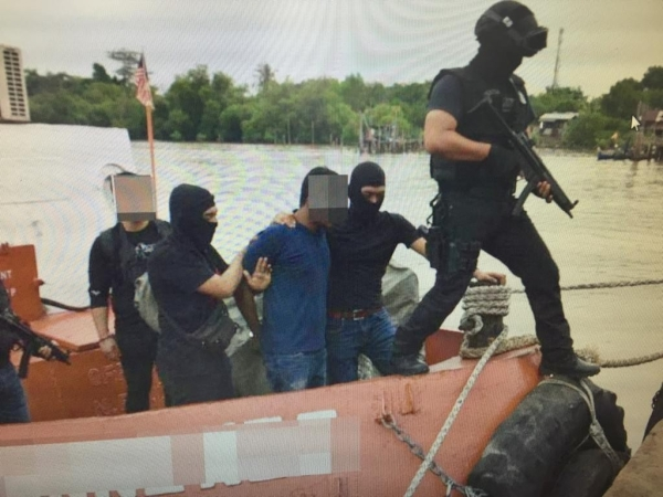 A team of E8 personnel detaining the Bangladeshi militant in Kuala Kedah recently.