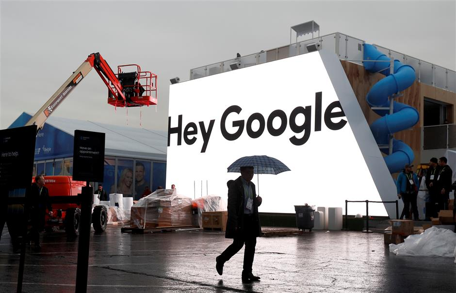 FILE PHOTO: A man walks through light rain in front of the Hey Google booth under construction at the Las Vegas Convention Center in preparation for the 2018 CES in Las Vegas, Nevada, U.S. January 8, 2018. REUTERS/Steve Marcus/File Photo                         GLOBAL BUSINESS WEEK AHEAD