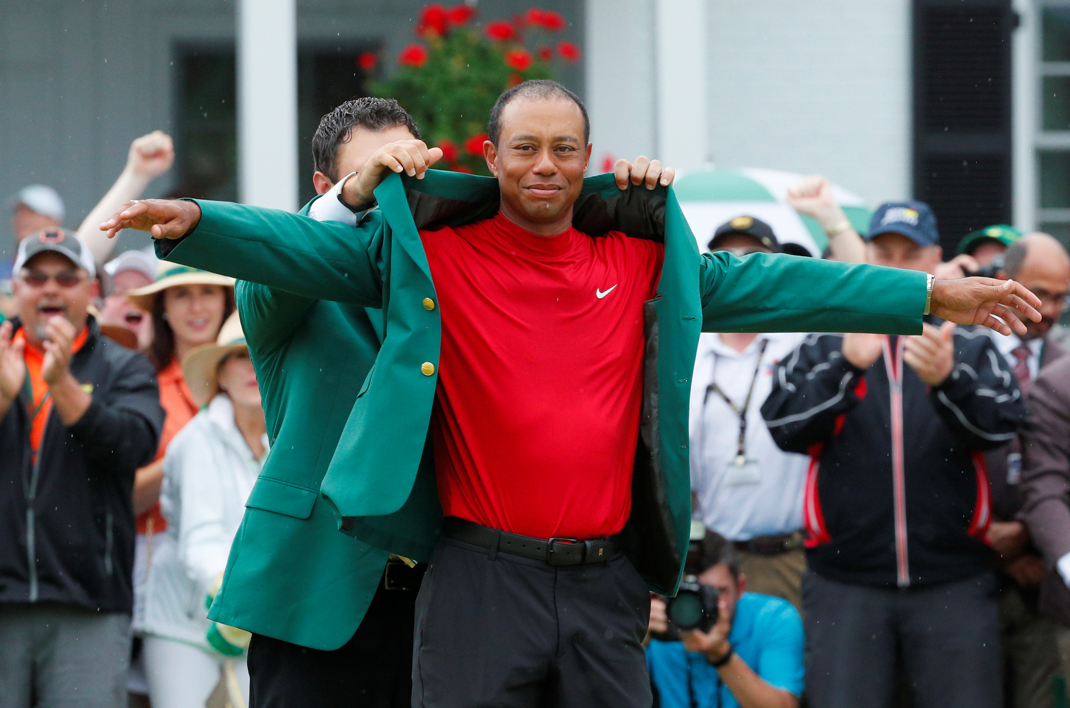 Golf - Masters - Augusta National Golf Club - Augusta, Georgia, U.S. - April 14, 2019 - Patrick Reed places the green jacket on Tiger Woods of the U.S. after Woods won the 2019 Masters. REUTERS/Brian Snyder
