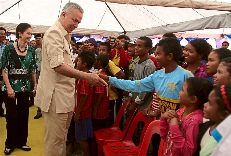 Royal greeting: Sultan ?Nazrin Shah (second from left) and ?Tuanku Zara Salim (left) being welcomed by orang asli children during their visit to Kampung Kuala Mu in Perak. — filepic