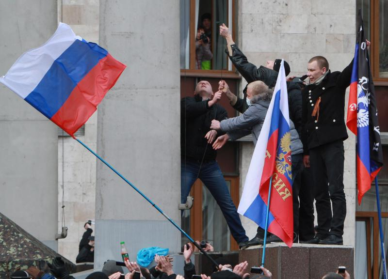 Demonstrators put up a Russian flag near a regional administration building in Donetsk, Ukraine, on March 1, 2014. Some 5,000 pro-Russian activists marched through the centre of Simferopol to parliament, while armed gunmen widen their patrols in the Crimean capita - EPA Photo.