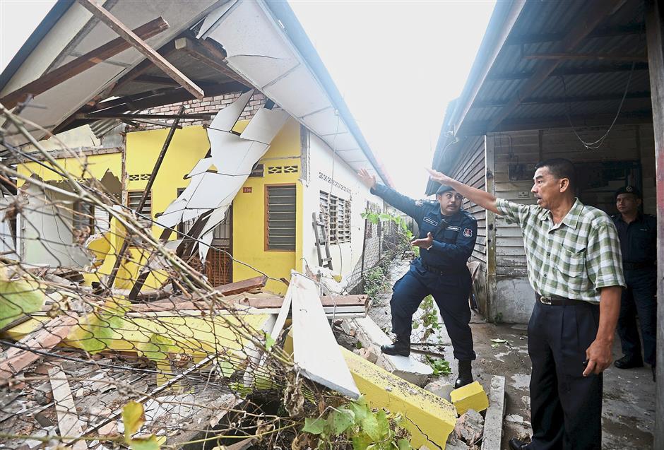 Demolition job: Kepong community service centre head Yee Poh Ping looking at DBKL officers demolishing the houses at parcel F, Jinjang Selatan Tambahan, Kuala Lumpur.