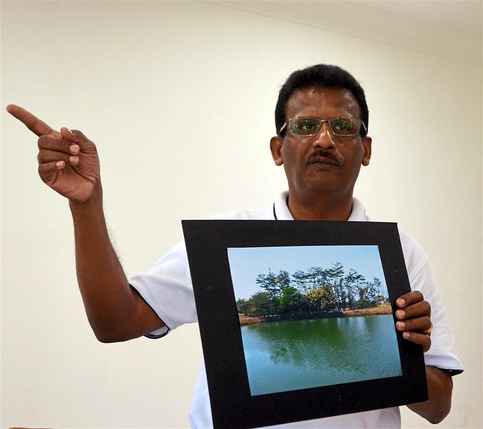 Ravindranathan showing a photo of the scenic retention pond in its original state.