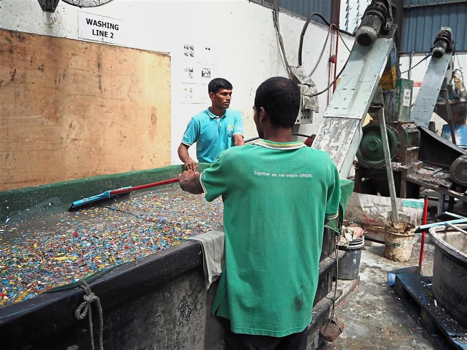 Valuable junk: Workers sorting out the plastic waste before it undergoes several processes to be made into plastic resin, which is then used to manufacture new products.