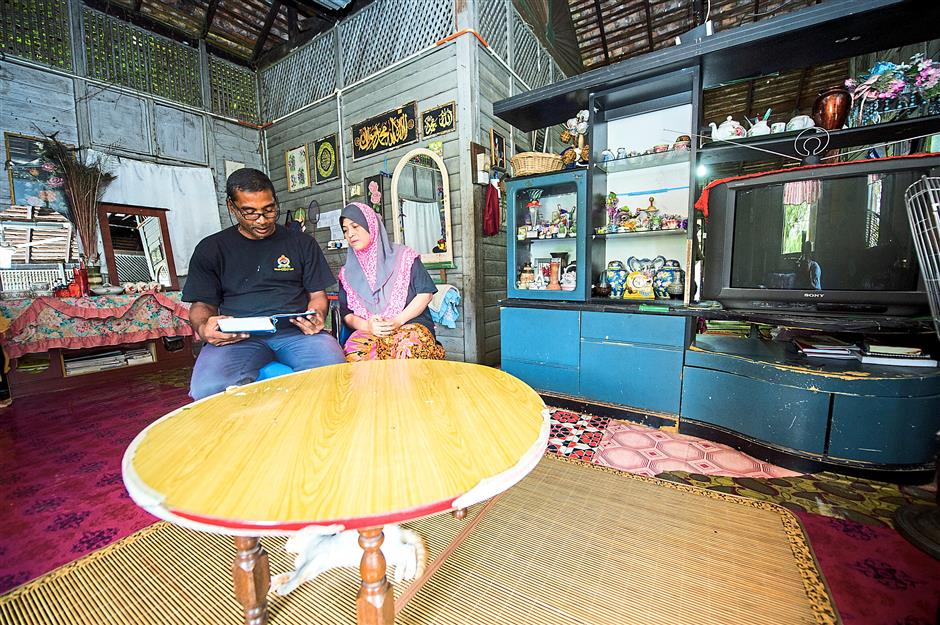 Normal on the inside: Wan Mamat and Amizar enjoying the cool comfort their 'green house' provides. — Bernama