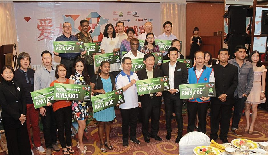 2 The recipients from charity homes, organisations and schools posing for a group pictures after receiving their financial aid in the 'Love in Malaysia 58' charity dinner at the Evergreen Laurel Hotel in Gurney Drive— CHAN BOON KAI/The Star