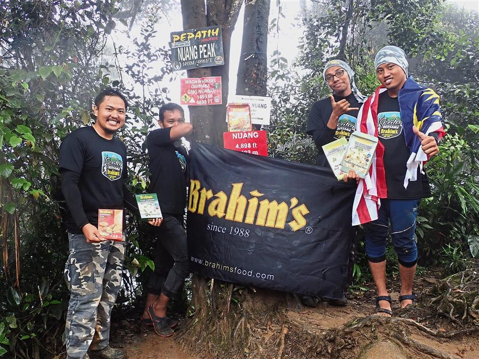 Members of the first expedition at the peak of Gunung Nuang holding packets of Brahim's adventure meal packs.