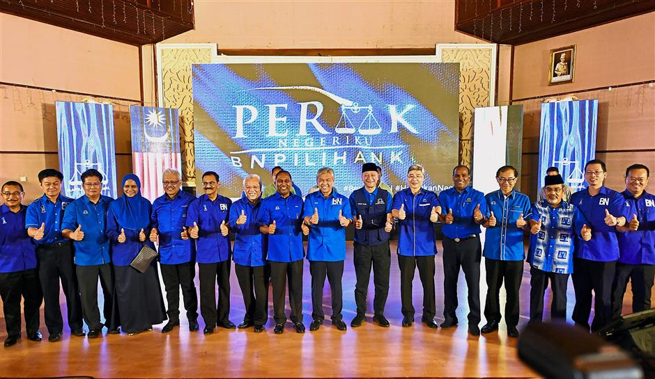 All set: Dr Ahmad Zahid and Dr Zambry (on Dr Ahmad Zahid's right) posing with Perak Barisan candidates after the announcement at the Mentri Besar's official residence in Ipoh. — Bernama