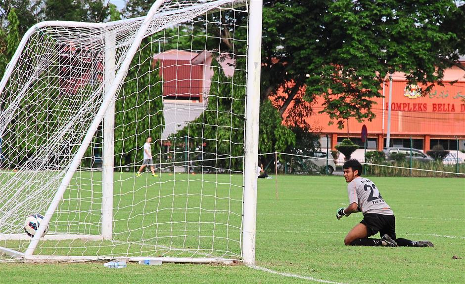 Bad moment: Police goalkeeper Muhammad Zulfadhli looking back in despair as he is  beaten by a penalty strike taken by Penang's Mohamed Faizal (not in picture).