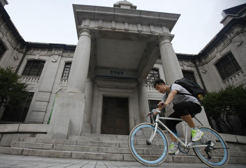 A man gets on a bicycle in front of the Bank of Korea in Seoul. The current account surplus in April stood at US$7.12bil, down 2.2% from a revised US$7.29bil in March, the Bank of Korea (BOK) says - Reuters Photo.