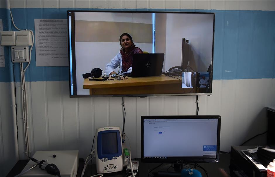 This photograph taken on October 20, 2017, Pakistani doctor Nadia Rasheed speaks during an interview with AFP on skype at a telemedicine online treatment centre run by the government of Khyber Pakhtukhwa in the remote Behali area in Mansehra district. In a remote northern Pakistani village surrounded by lush green hills, Mohammad Fayyaz brings his two-year-old son to a clinic so that a female doctor sitting hundreds of kilometres away can examine him. / AFP PHOTO / AAMIR QURESHI / TO GO WITH: Pakistan-health-technology, FEATURE by Sajjad Tarakzai