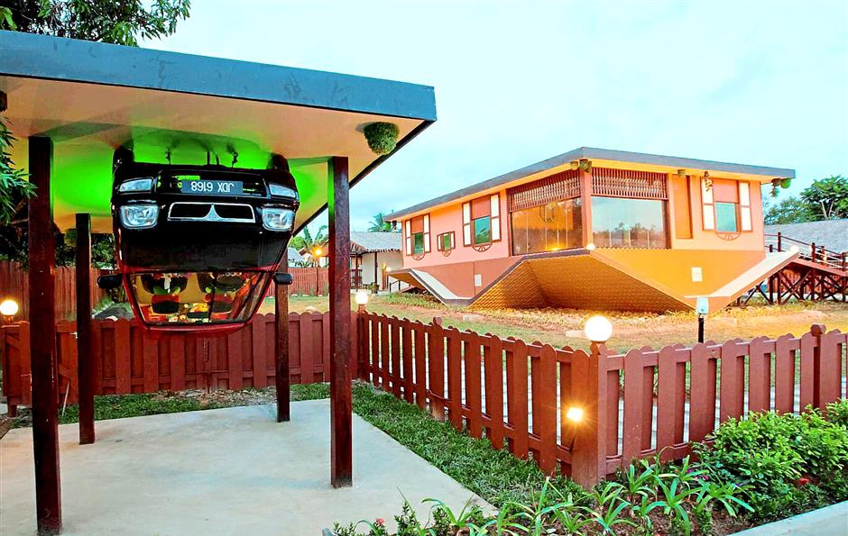 Curious attraction: Tamparuli's upside down house comes complete with an upside down car parked upside down inside its garage.