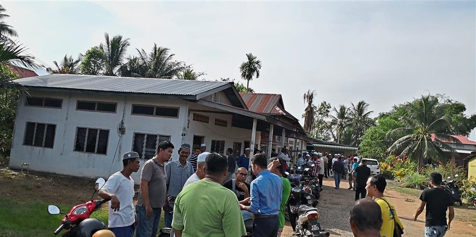Scene of the crime: Villagers gathering outside the house where the attack took place in Yan.
