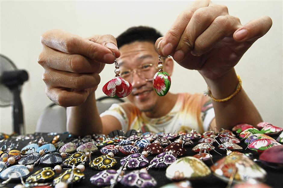 Goh Chiu Kuan showing the handmade clam earrings with different cloth motifs in the Artisan Market and Garage Sale at The Star Pitt St in George Town.StarPic by :LIM BENG TATT/THE STAR/ 02 Dec 2017.